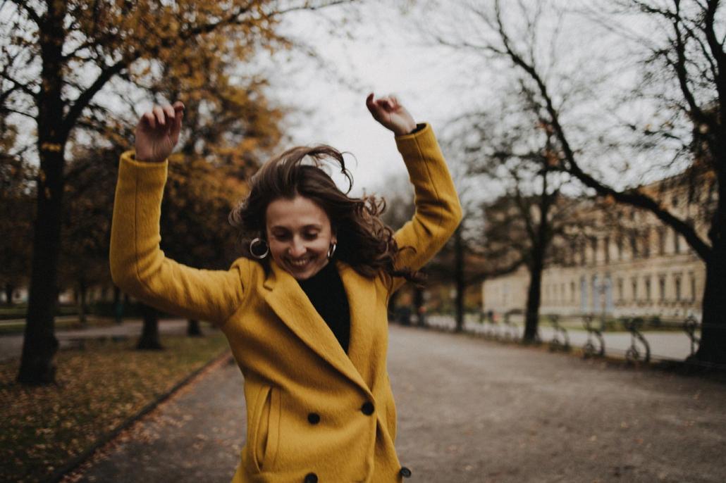 Portrait junge Frau im Herbst tanzend