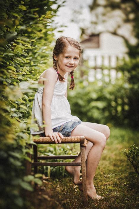 Mädchen sitzend im Garten